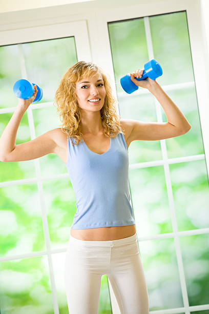 Young happy woman exercising with dumbbells at home stock photo