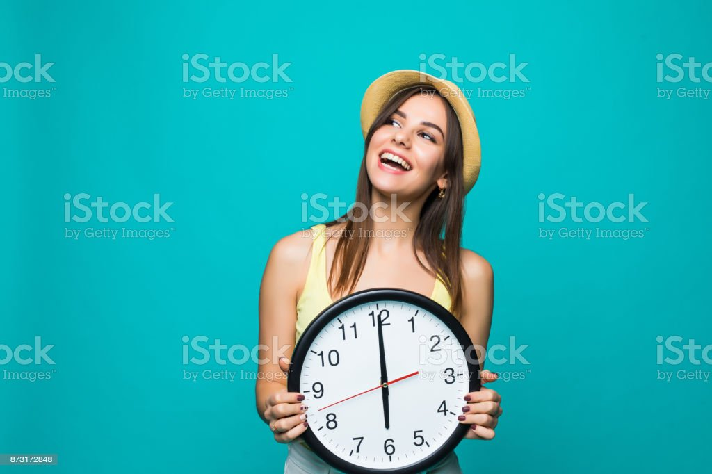 Young happy woman holding a clock with 12 clock on a green background. Portrait of positive pretty young woman with at wall clock over white background stock photo