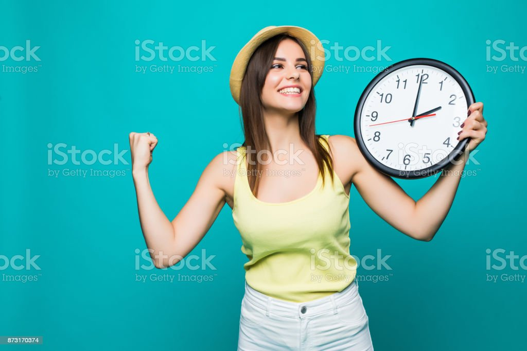 Young happy woman holding a clock with 2 clock on a green background stock photo