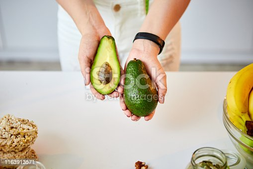 istock Young happy woman holding avocado for making salad in the beautiful kitchen with green fresh ingredients indoors. Healthy food and Dieting concept. Loosing Weight 1163913571