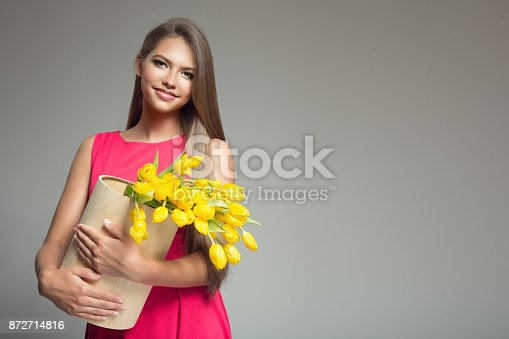 istock Young happy woman holding basket with yellow tulips. Gray background. 872714816