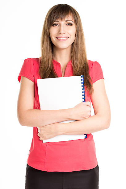 Young happy woman holding exercise book or course book Young happy woman in red shirt holding exercise book or course book. Pretty businesswoman with notebook isolated on white background sergionicr stock pictures, royalty-free photos & images