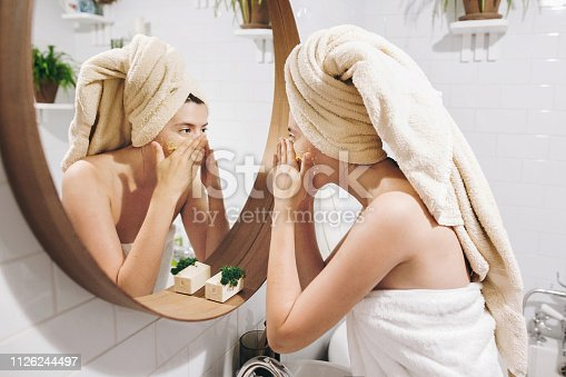 Young happy woman in towel applying organic face scrub and looking at round mirror in stylish bathroom. Girl making facial massage, peeling and cleaning skin on face. Skin Care and Hygiene