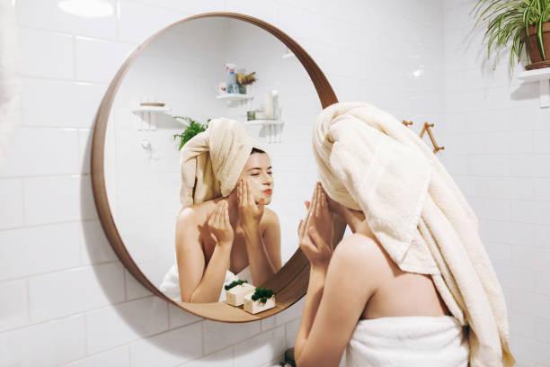 junge glückliche frau handtuch gesichtsmassage mit bio gesicht peeling machen und in stilvollen badezimmer spiegel betrachten. mädchen peeling creme, peeling und reinigung haut anwenden. haut-& körperpflege - feminine badezimmer stock-fotos und bilder