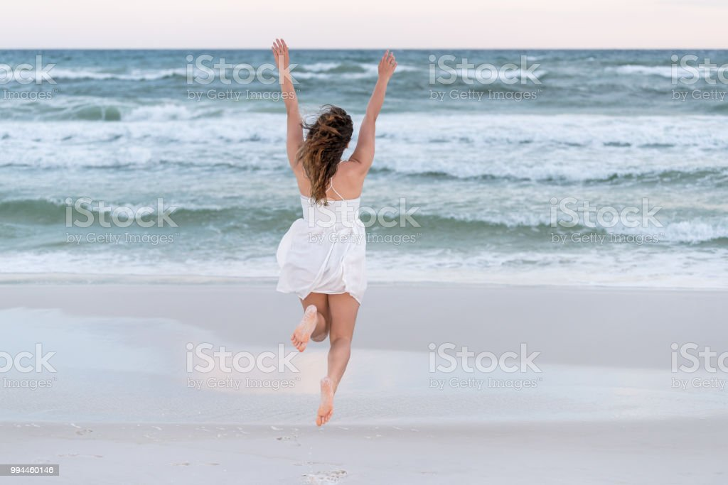 Young happy woman in white dress on beach pink sunset in Florida...