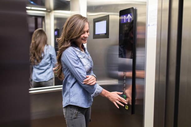 young happy woman inside of an elevator. - ascensore foto e immagini stock