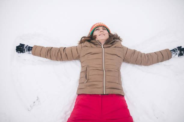 junge glückliche frau scherz auf schnee im wintertag - damen hosen angels stock-fotos und bilder