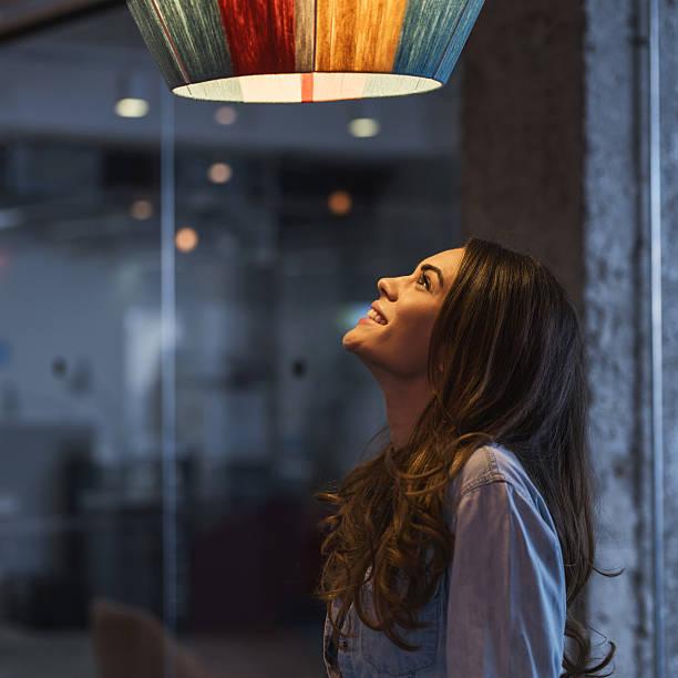 młoda szczęśliwa kobieta patrząc na światło. - żyrandol sprzęt oświetleniowy zdjęcia i obrazy z banku zdjęć