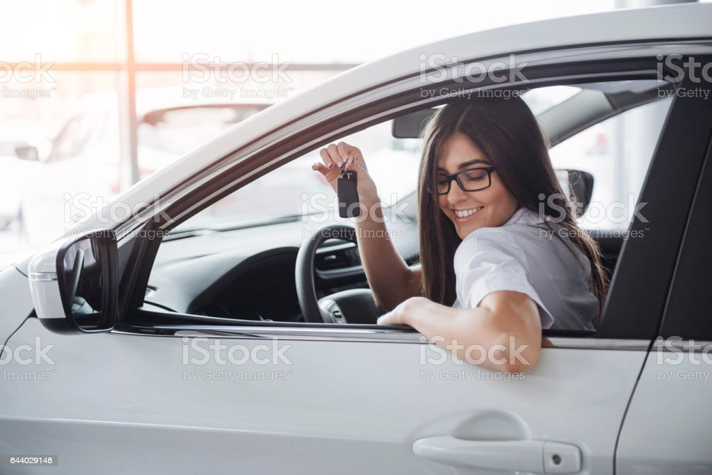 Young happy woman near the car with keys in hand stock photo
