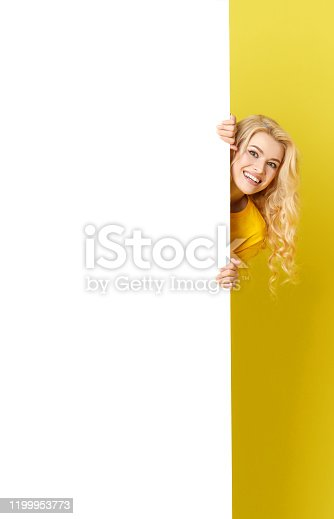 1168002879 istock photo Young happy woman peeks out from behind a white banner on a yellow background. Point to an empty blank on a form, a copy space for text. vertical shot 1199953773