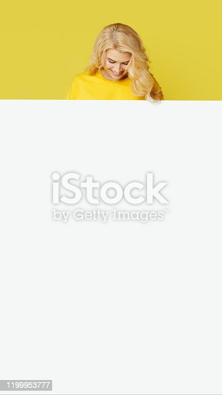 1168002879 istock photo Young happy woman peeks out from behind a white banner on a yellow background. Point to an empty blank on a form, a copy space for text. vertical shot 1199953777