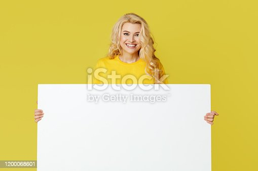 1168002879 istock photo Young happy woman peeks out from behind a white banner on a yellow background. Point to an empty blank on a form, a copy space for text. Horizontal shot 1200068601