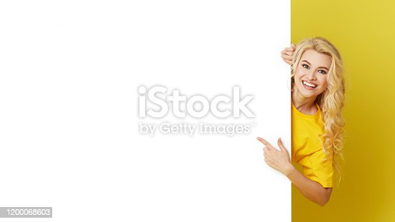 1168002879 istock photo Young happy woman peeks out from behind a white banner on a yellow background. Point to an empty blank on a form, a copy space for text. Horizontal shot 1200068603