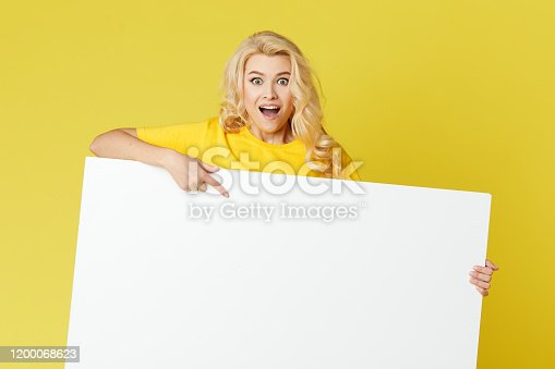 1168002879 istock photo Young happy woman peeks out from behind a white banner on a yellow background. Point to an empty blank on a form, a copy space for text. Horizontal shot 1200068623