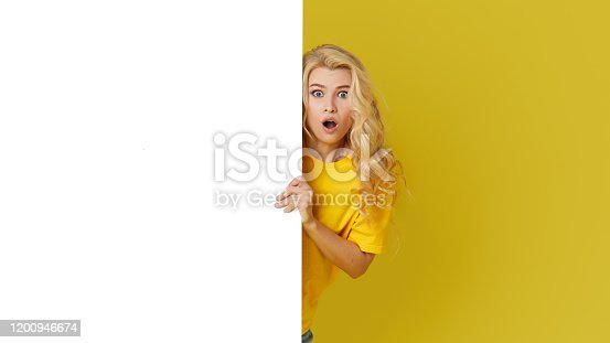 1168002879 istock photo Young happy woman peeks out from behind a white banner on a yellow background. Point to an empty blank on a form, a copy space for text. Horizontal shot 1200946674