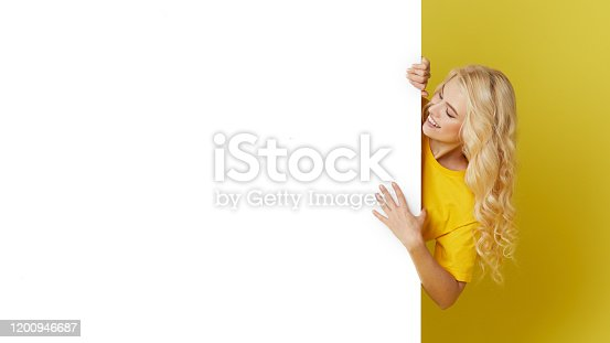 1168002879 istock photo Young happy woman peeks out from behind a white banner on a yellow background. Point to an empty blank on a form, a copy space for text. Horizontal shot 1200946687