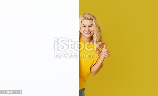 1168002879 istock photo Young happy woman peeks out from behind a white banner on a yellow background. Point to an empty blank on a form, a copy space for text. Horizontal shot 1200946714