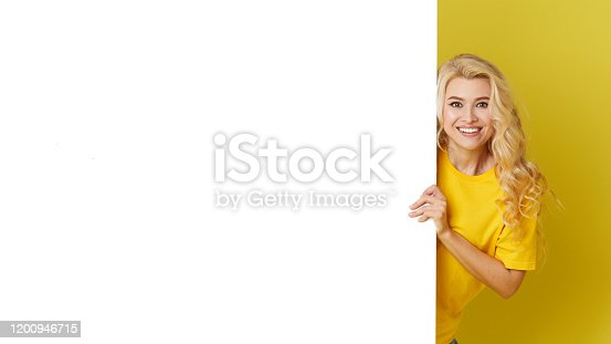 1168002879 istock photo Young happy woman peeks out from behind a white banner on a yellow background. Point to an empty blank on a form, a copy space for text. Horizontal shot 1200946715