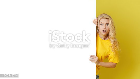 1168002879 istock photo Young happy woman peeks out from behind a white banner on a yellow background. Point to an empty blank on a form, a copy space for text. Horizontal shot 1200946744