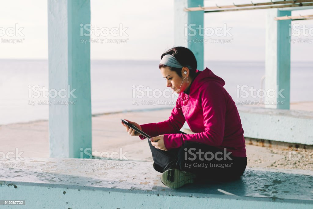 Young happy woman relaxing and listening music on the seafront. Concept relax and healtcare. stock photo