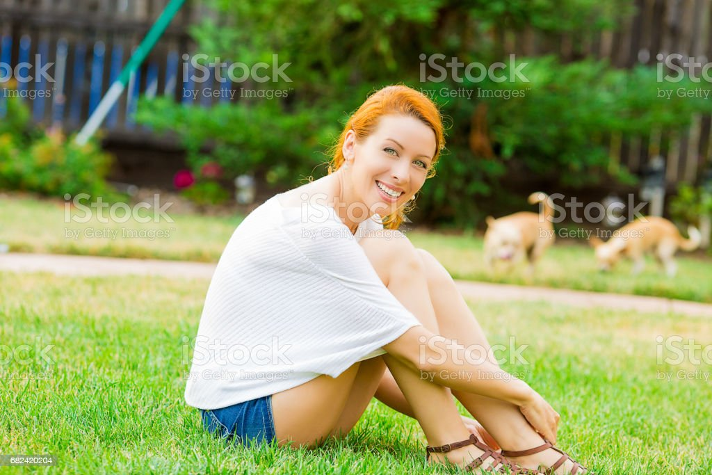 Young happy woman relaxing on green grass royalty-free stock photo