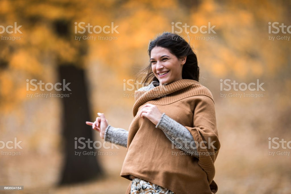 Young happy woman running during autumn day in nature. stock photo