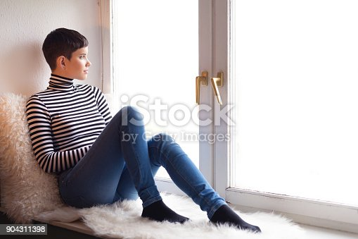 Young smiling woman sitting in the window and watching outdoor.