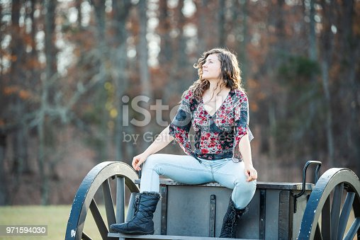 istock Young happy woman sitting manspreading spreading legs on old cannon carriage in Manassas National Battlefield Park in Virginia where Bull Run battle was fought 971594030