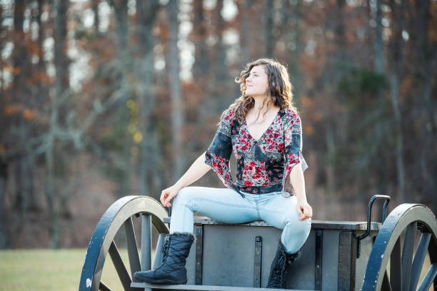 young happy woman sitting manspreading spreading legs on old cannon carriage in manassas national battlefield park in virginia where bull run battle was fought - civil war stock photos and pictures