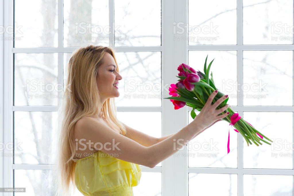 Glückliche Mädchen lächelnd mit Tulpe Haufen im gelben Kleid. – Foto