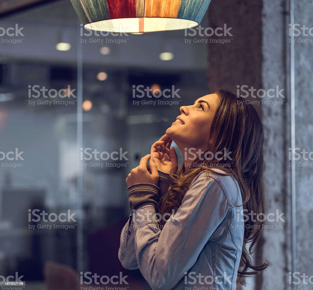 Young happy woman standing and looking at lamp. stock photo