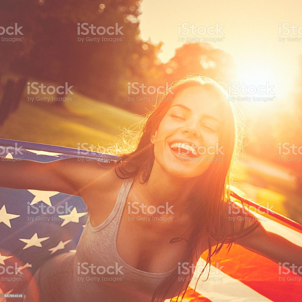 Young happy woman standing in a meadow holding american flag stock photo