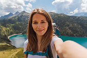 self portrait of a girl on a mountain peak during a sunny day. lake ritom