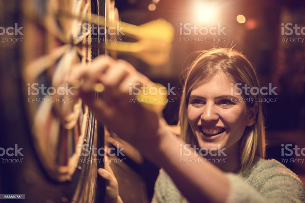 Young happy woman taking darts out of dart board. stock photo