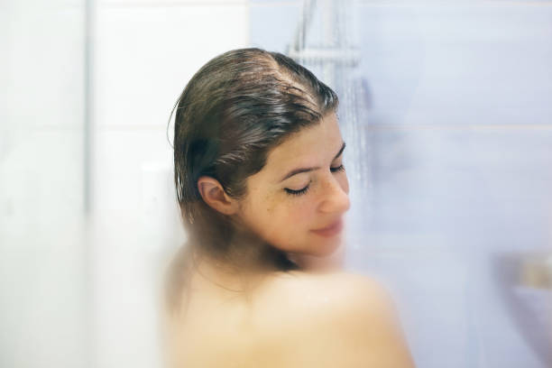 young happy woman taking shower at home or hotel bathroom. beautiful brunette girl washing her hair and enjoying relax time. body and skin hygiene, lifestyle concept - baths hot water stock photos and pictures