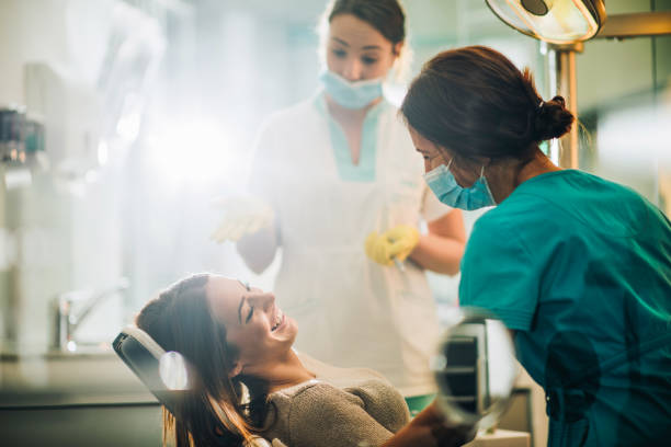 Young happy woman talking to a dentist before dental procedure. Smiling woman sitting in dentist chair and talking to her dentist before teeth examination. medical procedure stock pictures, royalty-free photos & images