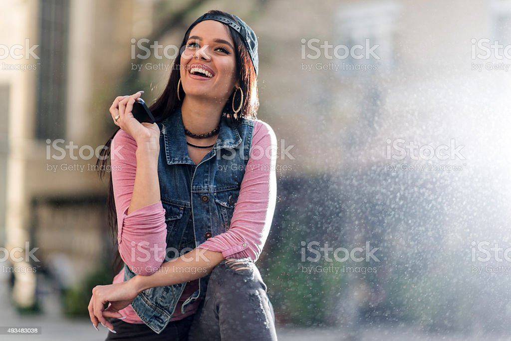 Young happy woman talking to someone over speaker. stock photo