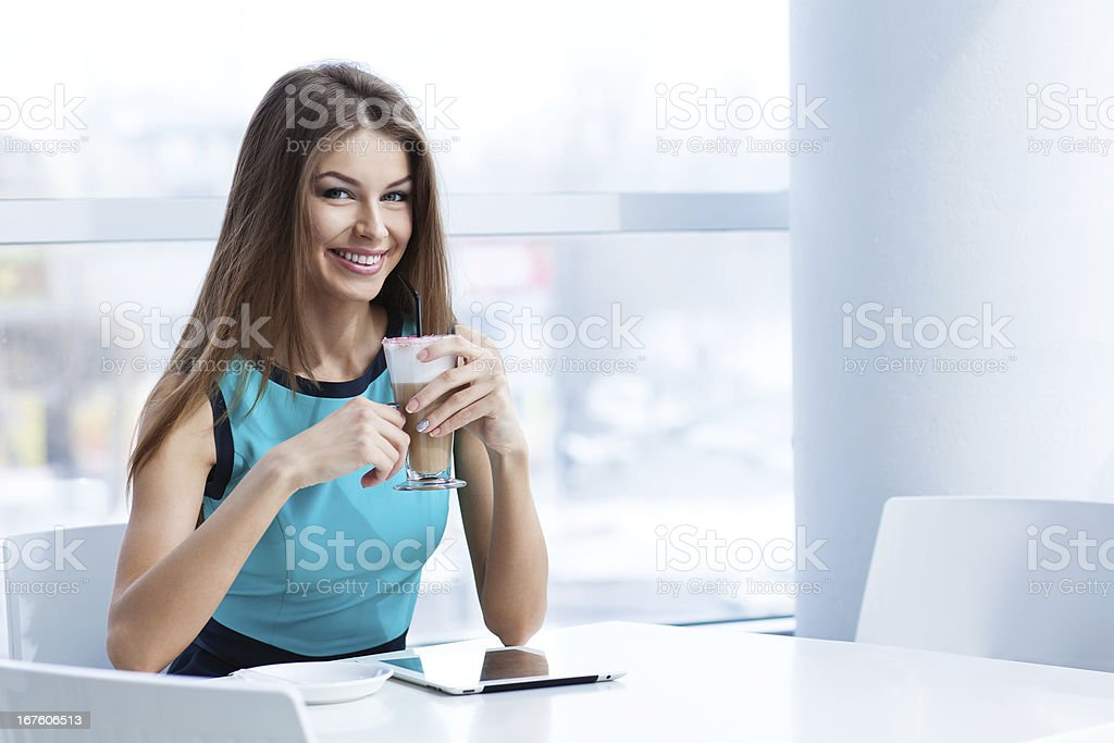 young happy woman using tablet computer in a cafe royalty-free stock photo