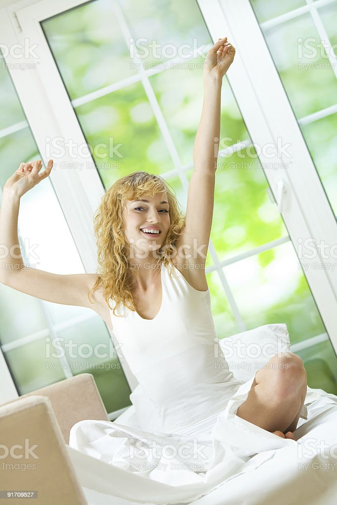 Young happy woman waking up at bedroom royalty-free stock photo
