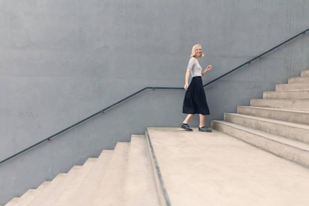 jeune femme heureuse, marche dans les escaliers de mur en béton - marches marches et escaliers photos et images de collection