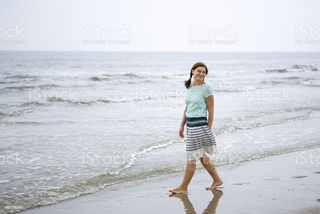 Young happy woman walking on the beach stock photo