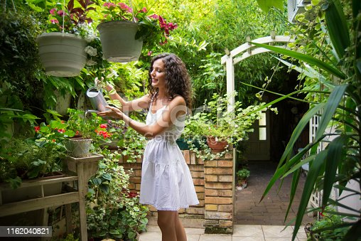 Young happy woman watering garden plants at her home in summer.