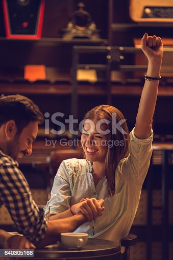 Smiling woman celebrating victory while arm wrestling with her boyfriend.