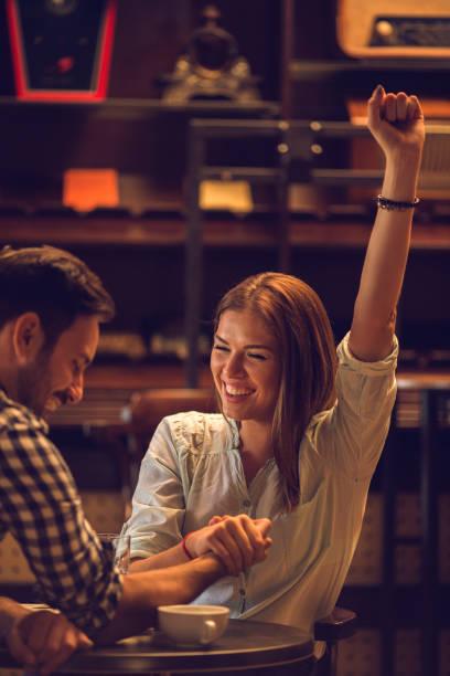 young happy woman winning in arm wrestling with boyfriend. - armdrücken stock-fotos und bilder