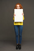Young happy woman with blank white paper. Redhead girl holding advertising sheet, copy space