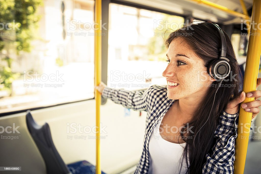 Young happy woman with ear phone on the bus stock photo