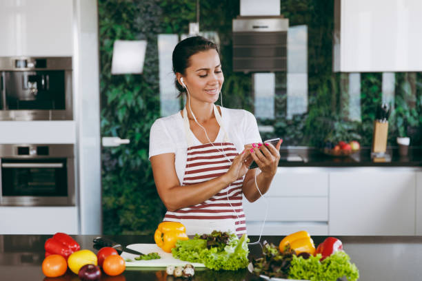 Young happy woman with headphones in the ears holding mobile phone in hands in kitchen. Vegetable salad. Dieting concept. Healthy lifestyle. Cooking at home. Prepare food stock photo