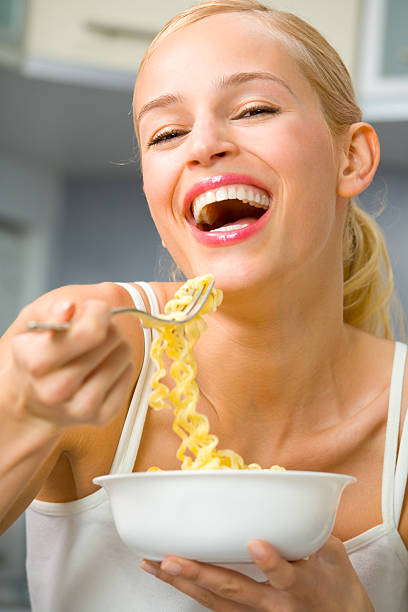 Young happy woman with plate of spaghetti at kitchen stock photo