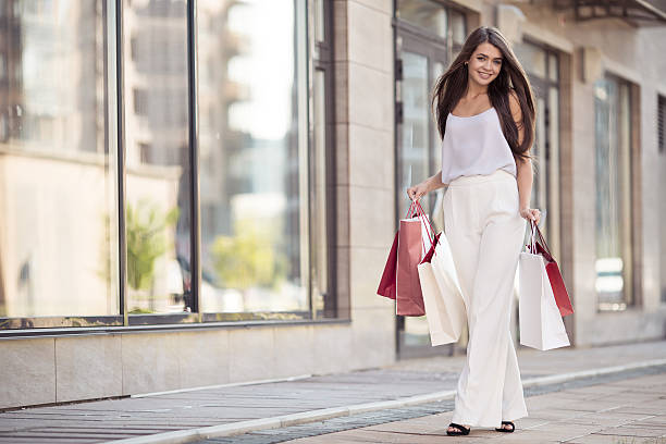 Young happy woman with shopping bags walking on street. stock photo
