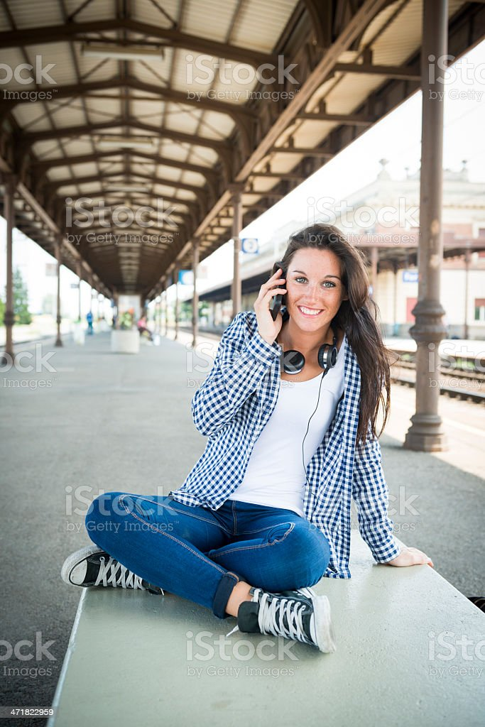Young happy woman with smart phone at the train station royalty-free stock photo